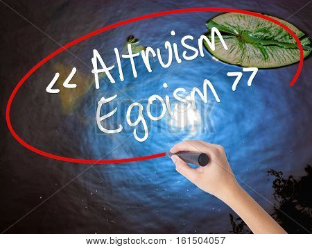 Woman Hand Writing Altruism - Egoism With Marker Over Transparent Board.