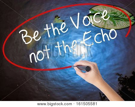 Woman Hand Writing Be The Voice Not The Echo With Marker Over Transparent Board.