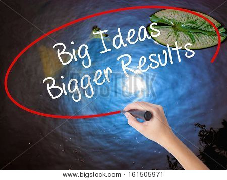 Woman Hand Writing Big Ideas Bigger Results  With Marker Over Transparent Board