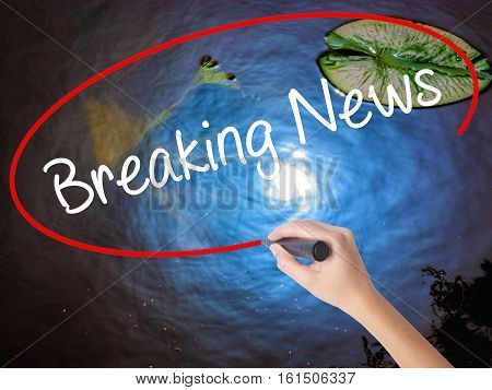 Woman Hand Writing Breaking News With Marker Over Transparent Board