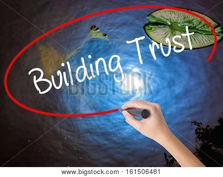 Woman Hand Writing Building Trust With Marker Over Transparent Board