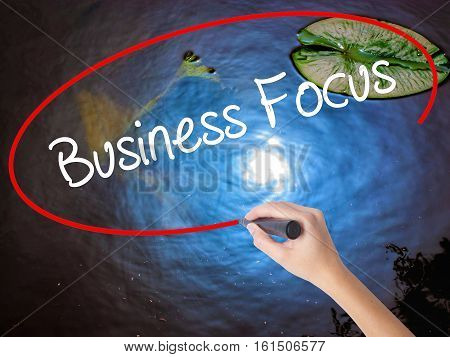 Woman Hand Writing Business Focus With Marker Over Transparent Board.