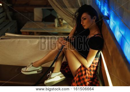 Beautiful Hipster Girl Sitting On The Couch And Smokes A Hookah.
