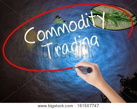 Woman Hand Writing Commodity Trading With Marker Over Transparent Board.