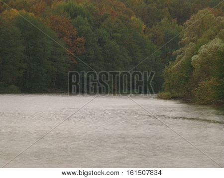 Autumn October gloomy rainy day, large pond and forest on a distant bank