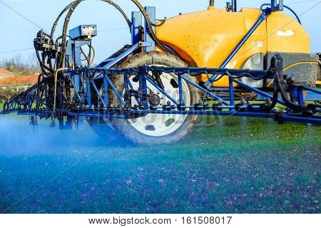 view of tractor spraying wheat field with sprayer