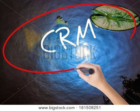 Woman Hand Writing Crm With Marker Over Transparent Board