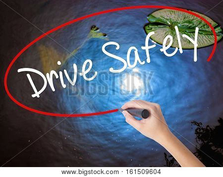 Woman Hand Writing  Drive Safely With Marker Over Transparent Board