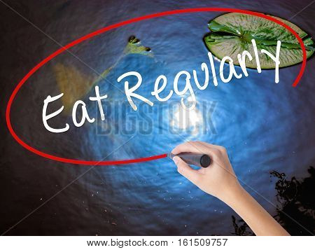 Woman Hand Writing Eat Regularly With Marker Over Transparent Board.