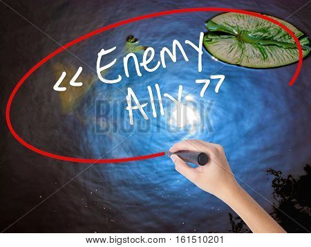 Woman Hand Writing Enemy - Ally With Marker Over Transparent Board.