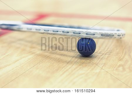 Close up of a squash racket and ball on the wooden background. Racquetball equipment. Squash ball between squash racket and floor on the court. Photo with toning and selective focus