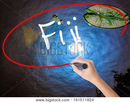 Woman Hand Writing Fiji  With Marker Over Transparent Board.