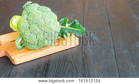 Broccoli on chopping block on wooden background