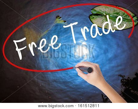 Woman Hand Writing Free Trade With Marker Over Transparent Board