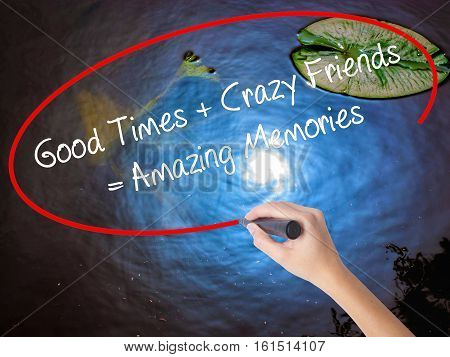 Woman Hand Writing Good Times + Crazy Friends = Amazing Memories With Marker Over Transparent Board