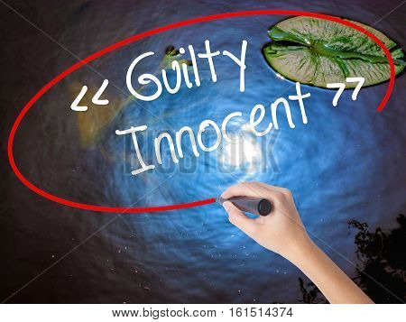 Woman Hand Writing Guilty - Innocent With Marker Over Transparent Board.