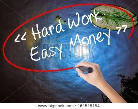Woman Hand Writing Hard Work - Easy Money With Marker Over Transparent Board.