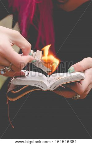 Young witch with pink hair is burning pages of her spellbook