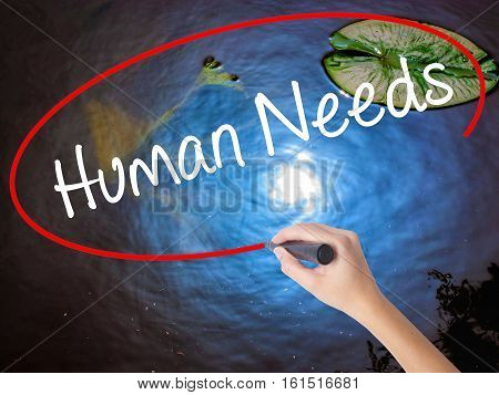 Woman Hand Writing Human Needs With Marker Over Transparent Board.