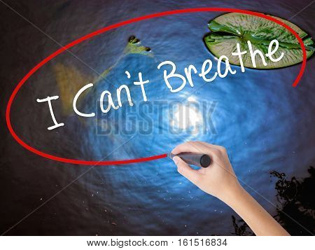 Woman Hand Writing I Can't Breathe  With Marker Over Transparent Board