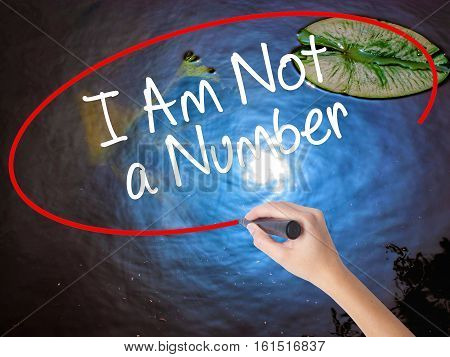 Woman Hand Writing I Am Not A Number With Marker Over Transparent Board