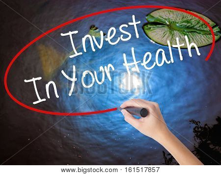 Woman Hand Writing Invest In Your Health With Marker Over Transparent Board.