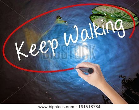 Woman Hand Writing Keep Walking With Marker Over Transparent Board