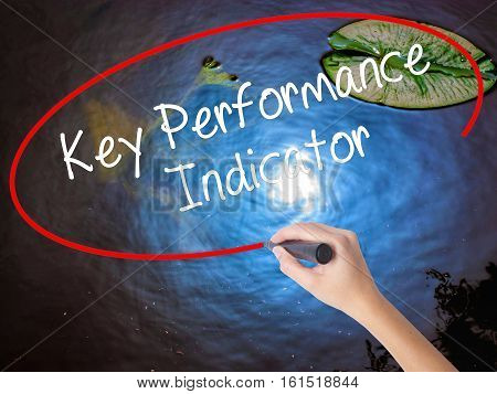 Woman Hand Writing Key Performance Indicator With Marker Over Transparent Board.