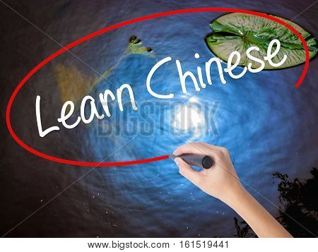 Woman Hand Writing Learn Chinese With Marker Over Transparent Board.