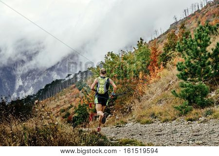 athlete runner running mountain marathon with walking poles