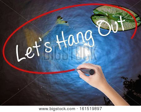 Woman Hand Writing Let's Hang Out With Marker Over Transparent Board