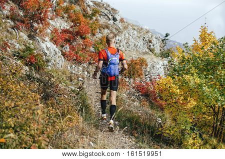 young male runner running on mountain trail with backpack