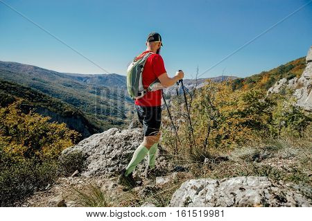 beard man with walking poles and backpacks go on a mountain trail