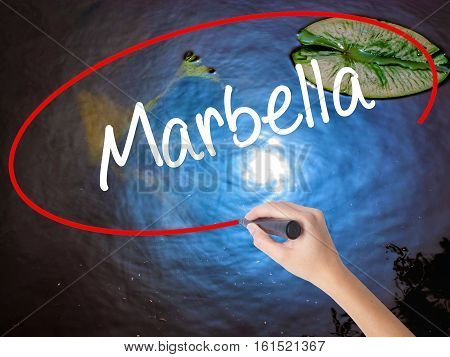 Woman Hand Writing Marbella With Marker Over Transparent Board