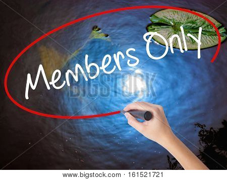 Woman Hand Writing Members Only With Marker Over Transparent Board.