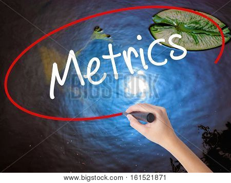 Woman Hand Writing  Metrics  With Marker Over Transparent Board