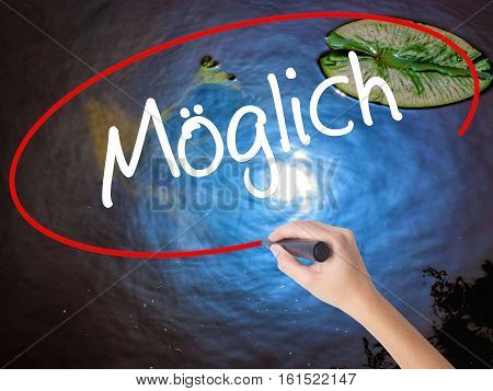 Woman Hand Writing Moglich (possible In German) With Marker Over Transparent Board.