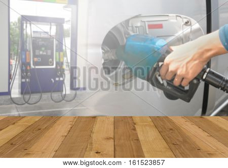 Wood floor and Hand holding Fuel nozzle pouring background