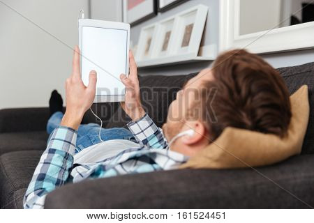 Image of back view of bristle man dressed in shirt in a cage print lies on sofa in home and using tablet computer while listening music with earphones. Looking at white display of tablet computer.