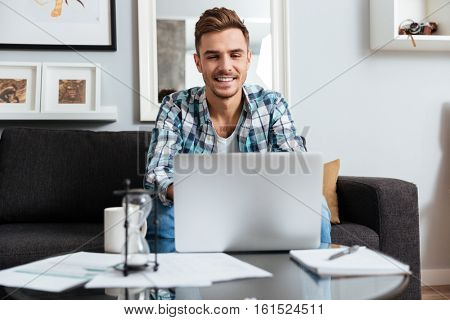 Picture of happy bristle man dressed in shirt in a cage print sitting on sofa in home and looking at laptop computer.