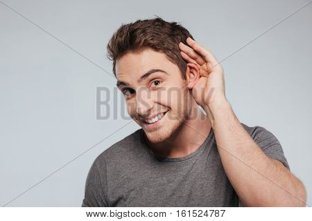Portrait of young casual man which overhears conversation over white background
