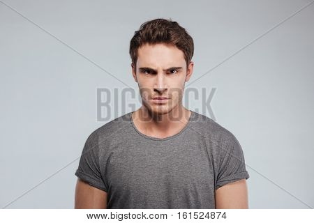 Close up of angry irritated young man looking camera over white background
