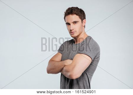 Portrait of a casual serious man standing with hands crossed isolated on a gray background