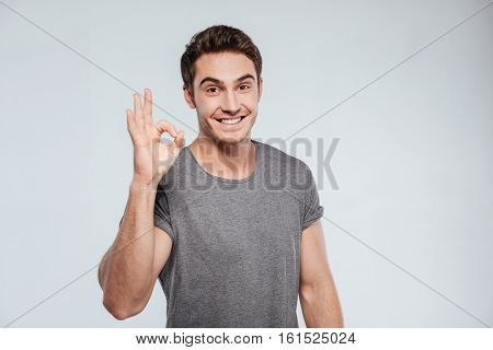 Portrait of a cheerful young man showing okay gesture isolated on the gray background