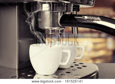 Preparing of aromatic espresso in modern coffee machine, closeup