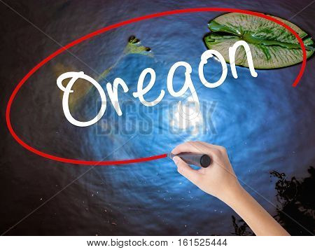 Woman Hand Writing Oregon With Marker Over Transparent Board