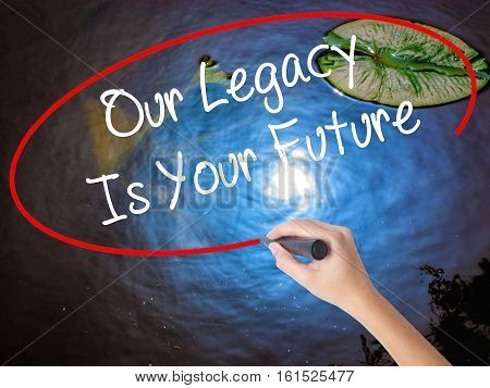 Woman Hand Writing Our Legacy Is Your Future  With Marker Over Transparent Board