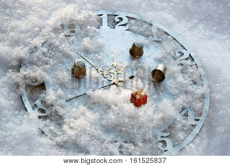 The game in a thimble on the clock in the snow before the New Year