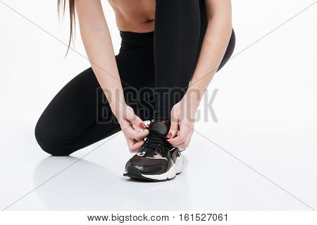 Cropped image of a sports female sitting and tying shoelace isolated on a white background