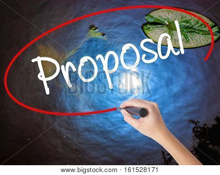 Woman Hand Writing  Proposal With Marker Over Transparent Board